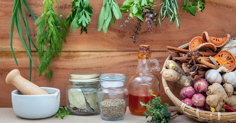 Jars of herbs, bottle of oil, roots and ginger and garlic with herbs hanging down